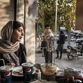 Maryam, 22, during a lunch break with typical iranian food (tadig rise and halim budenjun) and Pepsi Cola. Tehran, Iran. November 2014.