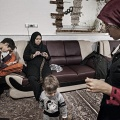 Reyhane, 21, is a shiite muslim woman, in her living room with her mother Zohre, doing the crochet, and the two brothers Ali and Mahdi. Nooshabad, Iran. December 2014.