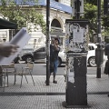"""Two Colombian men are attacking the papelitos on the street. The papelitos are like post-it, glued on poles, bins or on the walls of the streets, which with a cartoon drawing or the image of a half-naked woman, invite to call the number overwritten, describing the """" goods """"available: new, younger than 21 years, in promotion or high level. Buenos Aires, Argentina. January 2017."""